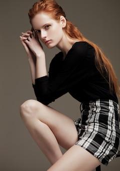 Teste de modelo com a jovem e bela modelo vestindo camisa preta e saia, sentado na cadeira em fundo cinza