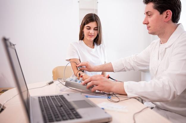 Teste de nervos do paciente usando eletromiografia em centro médico