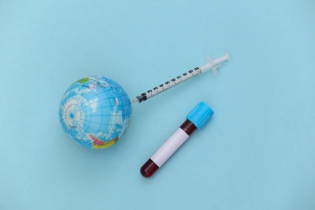 Teste de sangue global covid-19. tubo de ensaio com sangue, seringa com globo sobre fundo azul. vista do topo