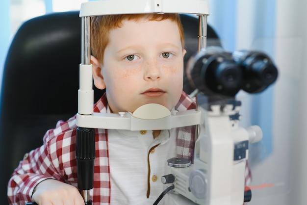 Teste de visão de menino com lâmpada de fenda binocular. verificando a retina de um close-up do olho de um adolescente. clínica oftalmológica