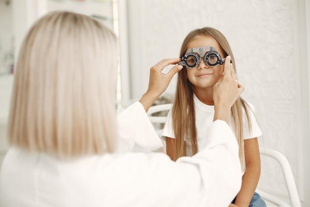 Teste oftalmológico infantil e exame oftalmológico. menina fazendo exame de olho, com foróptero. médico realiza exame de vista em criança