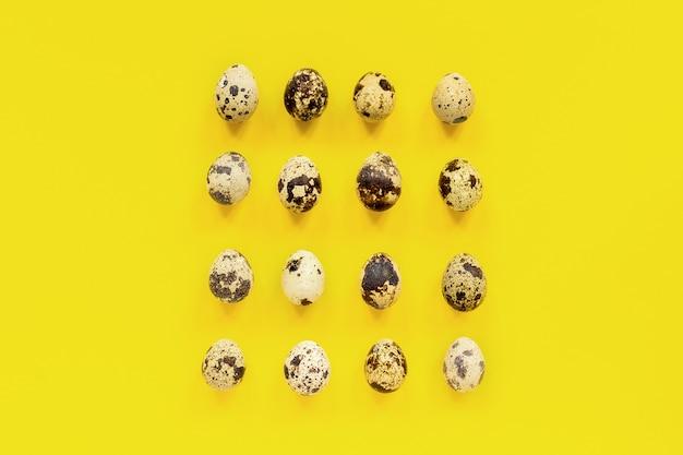 Teste padrão ajustado de ovos de codorniz no fundo de papel amarelo. conceito de páscoa.