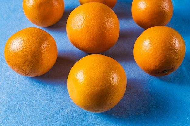 Teste padrão alaranjado da fruta com frutos maduros frescos no fundo azul.