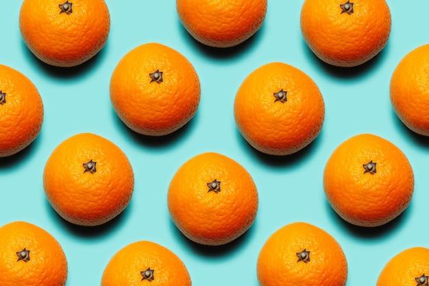 Teste padrão colorido de frutas frescas de tangerinas laranja em fundo de ciano ou água menta de cor.