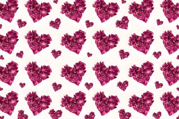 Teste padrão colorido de muitas pétalas de flores em forma de corações rosa pastel, isoladas no fundo branco.
