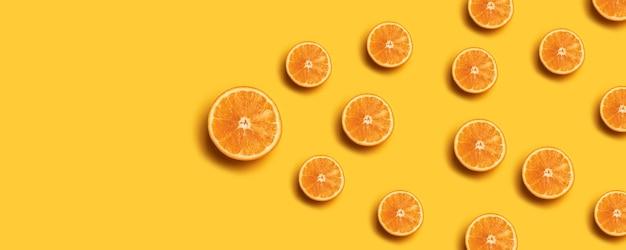 Teste padrão da fruta de fatias alaranjadas frescas no fundo amarelo.