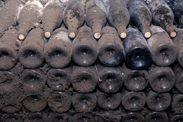 Teste padrão do close up da parte inferior de garrafas de vinho empoeiradas escuras velhas nas fileiras na adega da adega. cofre de conceito com velhos vinhos raros, garrafa rara de coleção exclusiva