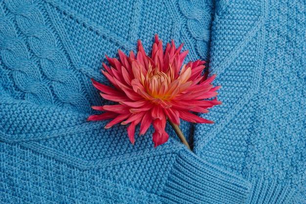 Teste padrão do close up feito malha colorido das camisolas. produto artesanal de lã merino. uma pilha de roupas dobradas com flores.