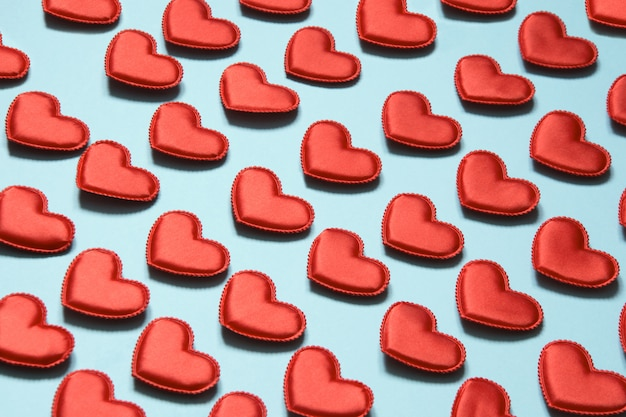 Teste padrão feito de corações vermelhos no azul. coração em estilo isométrico. cartão de dia dos namorados.