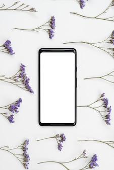 Teste padrão feito de flores rústicas na mesa com tela branca do telefone