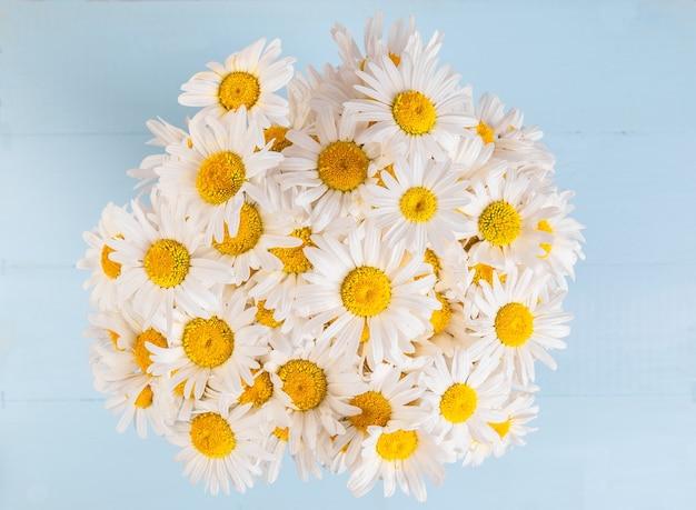 Teste padrão floral de verão com buquê de flor de camomila e margarida sobre azul vintage de madeira