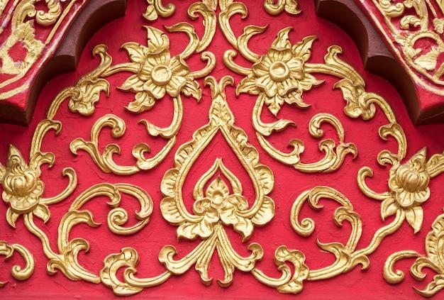 Teste padrão floral do estuque com a pintura dourada.