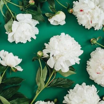 Teste padrão floral feito de flores de peônia branca, folhas verdes, galhos em verde