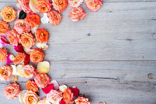 Teste padrão floral, moldura feita de rosas sobre fundo de madeira. flat leigo, vista superior.