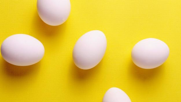Teste padrão liso do ovo da disposição da configuração no fundo pastel amarelo.