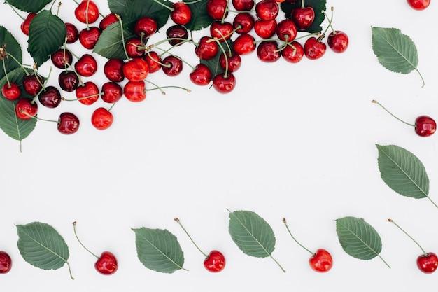 Teste padrão vermelho fresco da cereja e da folha no fundo branco.