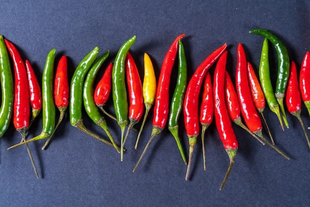 Teste padrão vermelho, verde e amarelo da configuração lisa das pimentas de pimentão sobre o fundo cinzento.