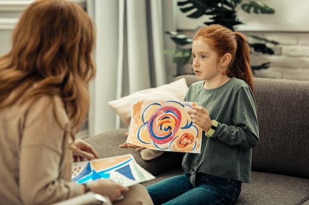 Teste psicológico. linda garota agradável segurando uma pintura colorida enquanto fala sobre ela