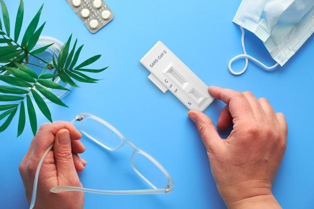 Teste rápido covid-19 na mão. fundo azul com planta de palma, óculos de leitura, pílulas e máscara facial. detecção sorológica de anticorpos igm e igg para o novo coronavírus sars-cov-2 causando covid-19.