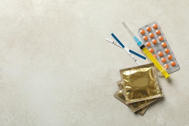 Testes de gravidez, seringa e comprimidos em superfície texturizada branca