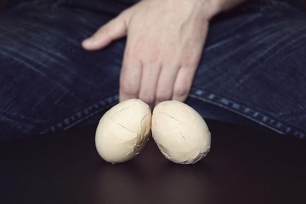 Testes masculinos - dor na virilha e relâmpago. o conceito de doença nos testículos masculinos. ovos quebrados são um símbolo de problemas com os testículos nos homens.