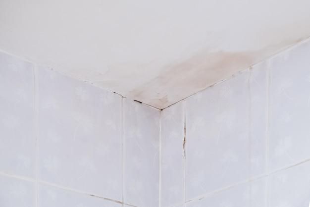 Teto branco com a mancha de água e o longo vazamento da chuva perto do canto da cozinha.