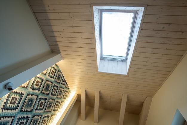 Teto de madeira em uma mansarda contemporânea com janela de sótão de superfície de tábuas decorativas.
