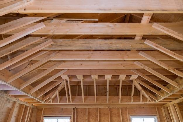 Teto de vigas de madeira com estrutura em construção dentro de casa residencial