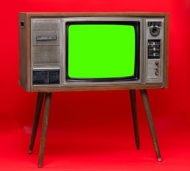 Tevê do vintage: aparelho de televisão retro velho isolado no fundo vermelho.