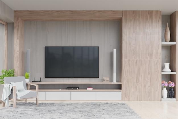 Tevê na parede na sala de visitas moderna com decoração e poltrona na parede de madeira do cimento.