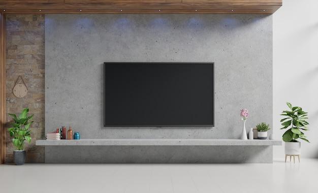 Tevê no cimento stan na sala de visitas moderna com lâmpada, tabela, flor e planta na parede do cimento.