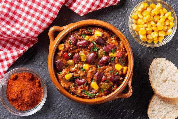 Tex mex tradicional mexicano, chili con carne em uma tigela sobre fundo de ardósia preta