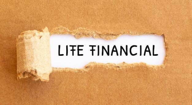 Text life financial aparecendo atrás de papel marrom rasgado.