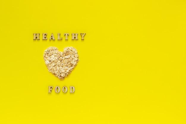 Text o alimento saudável e a aveia da farinha de aveia lasca-se no coração da forma no fundo amarelo.