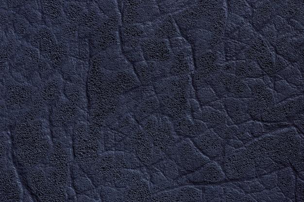 Têxtil de couro azul marinho escuro com textura e padrão, closeup.