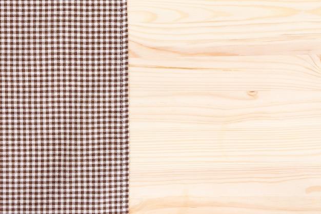 Têxtil de pano marrom em fundo de madeira
