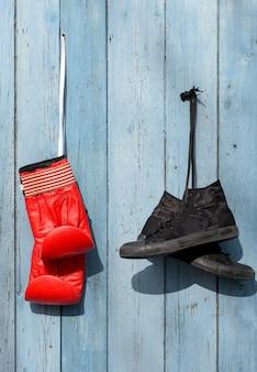Têxtil preto usado tênis e luvas de boxe de couro vermelho