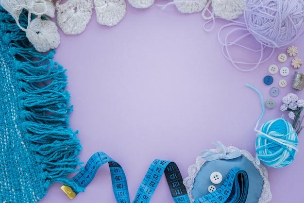 Têxtil tricotado; bola de lã; botão; fita métrica no fundo roxo com espaço de cópia para escrever o texto
