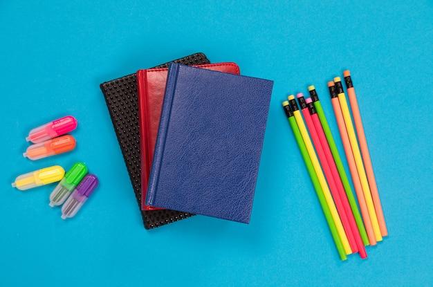Textliners e giz de cera coloridos e três planejadores em capas de couro estão deitados na superfície azul pálido isolada