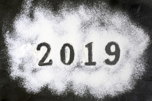 Texto 2019 feito com farinha com decorações em um fundo preto. feliz natal, feliz n