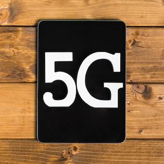 Texto 5g no tablet na superfície de madeira