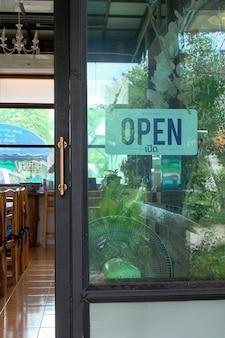 Texto aberto no sinal da porta e desligando na porta de vidro da cafeteria