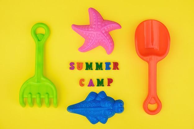 Texto acampamento de verão e brinquedos das crianças para jogos de verão na caixa de areia ou na praia arenosa