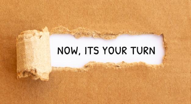 Texto agora, é sua vez aparecendo atrás de papel marrom rasgado