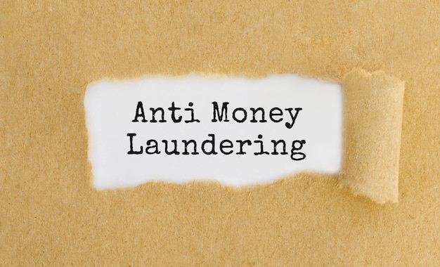 Texto anti-lavagem de dinheiro aparecendo atrás de papel pardo rasgado.