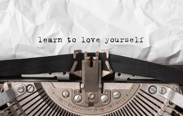 Texto aprenda a se amar digitado em uma máquina de escrever retrô