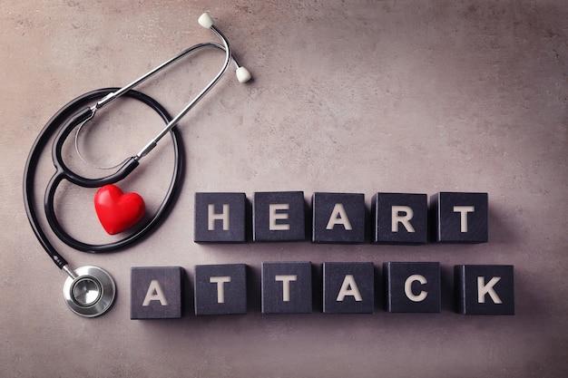 Texto ataque de coração feito de cubos de madeira e estetoscópio na cor de fundo