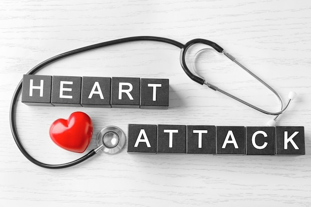 Texto ataque de coração feito de cubos e estetoscópio sobre fundo de madeira