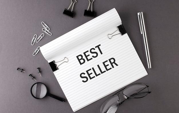 Texto best seller escrito em notebook e ferramentas de escritório em fundo cinza