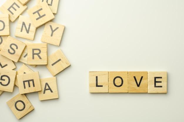 Texto blocos de madeira que soletram a palavra amor no fundo branco